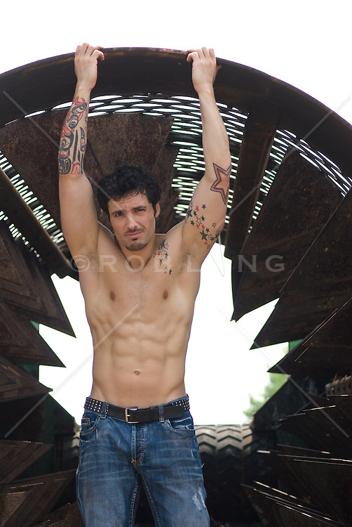 Shirtless young man with tattooed arms standing in an abandoned iron thrasher