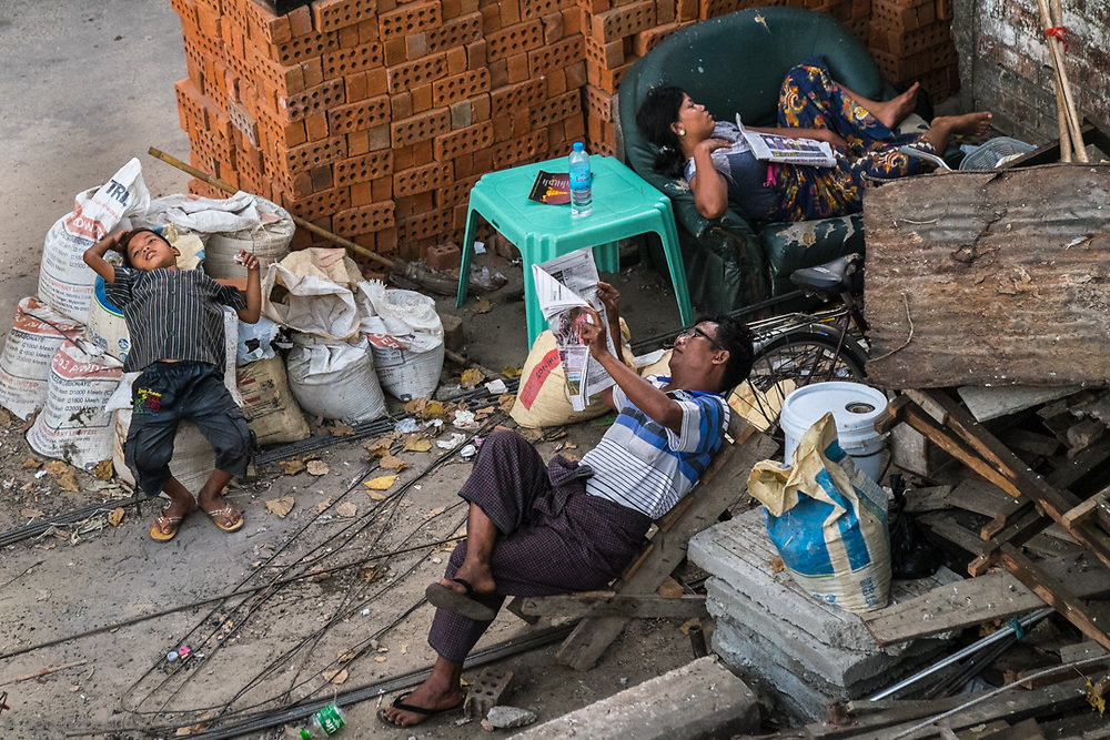 Resting in Chaos. Thanks to a nearby bridge i was able to isolate this family relaxing in the street of Yangon, Myanmar.<br />