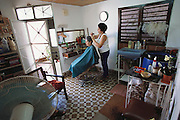 Eulina Costa Allouis has turned the front room of her small apartment into a beauty parlor. Originally, she did the business on the roof of their home, out of sight from prying government eyes as no one was supposed to have a private business. Restrictions are less rigorous these days. Marianao district, Cuba. From coverage of revisit to Material World Project family in Cuba, 2001.