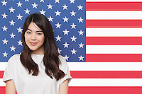 Portrait of smiling mixed race young woman against American flag