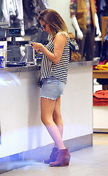 Caroline Flack out shopping in north London. The TV presenter wearing a see-through stripy top, short denim skirt and a pair of brown wedge boots bought a top from GAP and grab a Frappuccino before heading home... UK. 10/08/2012<br />