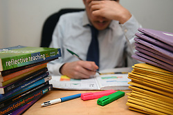 File photo dated 05/03/17 of a teacher next to a pile of classroom books. A study published in Educational Review suggests performance targets, curriculum changes, and heavy workload is harming the mental health of teachers in England and Wales.