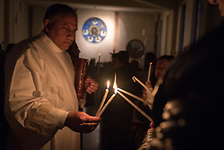 20 April 2019, Jerusalem: Deacon Bassam Ghattas (left) lets the light pass from one candle to another during Holy Saturday service at Saint James' Church in Beit Hanina, Jerusalem.