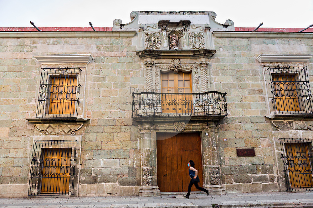 A young woman runs past the Museum of Contemporary Art on the Alcala in the historic district Oaxaca, Mexico.