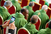 Vatican City oct 4th 2015, opening mass in St Peter's Basilica for  the bishops synod on family. In the picture a bishop with a smartphone