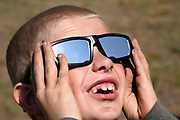 Cooper Jackson tries out his new solar glasses in a designated eclipse viewing area in a campground near Guernsey, Wyoming U.S. August 20, 2017.  REUTERS/Rick Wilking