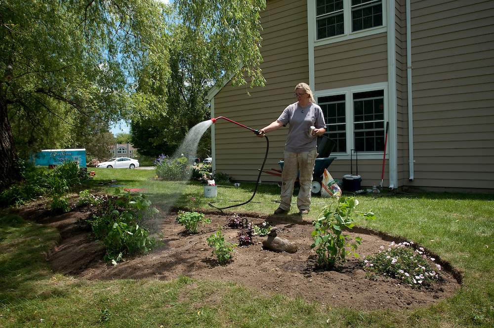 Brenda Cooke watering the almost finished garden at Kathleen Chase's house...Hope in Bloom is a non-profit organization that plants flower or vegetable gardens free of charge throughout Massachusetts at the homes of women and men undergoing treatment for breast cancer. ..Healing gardens have been proven to be therapeutic sanctuaries offering both comfort and hope to meet the emotional and psychological needs of patients and their families...Photographer: Chris Maluszynski /MOMENT