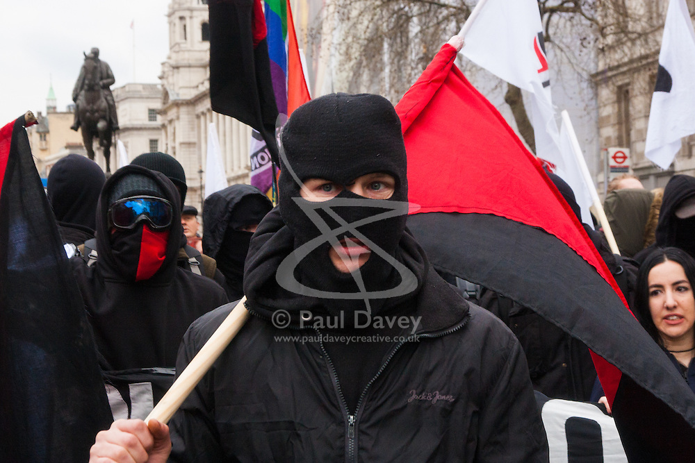 Whitehall, London, April 4th 2015. As PEGIDA UK holds a poorly attended rally on Whitehall, scores of police are called in to contain counter protesters from various London anti-fascist movements. PICTURED: A masked anti-fascist marches towards the PGIDA rally.