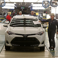 A Toyota team member places a manifest on a new Corolla as it comes off the line on Friday afternoon.