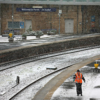 A ScotRail employee spreads salt onto the platforms at Perth Railway station this morning after overnight snow and ice which continued to fall into the day...27.12.14<br /> Picture by Graeme Hart.<br /> Copyright Perthshire Picture Agency<br /> Tel: 01738 623350  Mobile: 07990 594431