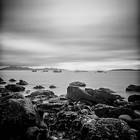 Fishing boats from Elgol beach, long exposure, rocks in foreground.