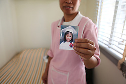 A Filipino woman standing in her room at her employer's home holds a picture of her daughter in the Philippines who she hasn't seen in two years.