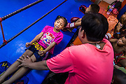 "18 DECEMBER 2104 - BANGKOK, THAILAND: A girl who wants to box does sit up exercises on the apron of the ring at the Kanisorn gym. The Kanisorn boxing gym is a small gym along the Wong Wian Yai - Samut Sakhon train tracks. Young people from the nearby communities come to the gym to learn Thai boxing. Muay Thai (Muai Thai) is a Thai fighting sport that uses stand-up striking along with various clinching techniques. It is sometimes known as ""the art of eight limbs"" because it is characterized by the combined use of fists, elbows, knees, shins, being associated with a good physical preparation that makes a full-contact fighter very efficient. Muay Thai became widespread internationally in the twentieth century, when practitioners defeated notable practitioners of other martial arts. A professional league is governed by the World Muay Thai Council. Muay Thai is frequently seen as a way out of poverty for young Thais and Muay Thai camps and schools are frequently crowded. Muay Thai professionals and champions are often celebrities in Thailand.     PHOTO BY JACK KURTZ"