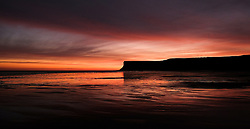 © Licensed to London News Pictures.25/10/15<br /> Saltburn, UK. <br /> <br /> Stunning colours light up the morning sky over the beach and cliffs at Saltburn in Cleveland. <br /> <br /> Photo credit : Ian Forsyth/LNP