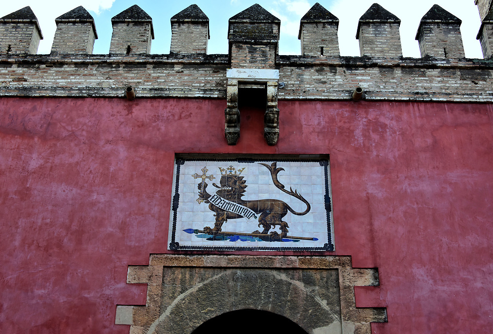 Lion&rsquo;s Gate at Real Alc&aacute;zar in Seville, Spain<br /> Real Alc&aacute;zar is the epicenter of 2,000 years of Sevilla&rsquo;s history. The earliest building on this site dates from the 1st century, followed by a basilica built by the Visigoths (418 &ndash; 711). They were conquered by Muslim Barbers early in the 8th century. 100 years later, the Umayyads constructed an alcazaba here. This walled fortress began evolving into a palace by Al-Mu&rsquo;tamid ibn Abbad during the 11th century. But it was the Almohads, starting in the 12th century, who did the most elaborate construction. Their palace was named Al-Muwarak. After their defeat in the mid-13th century, Spanish kings expanded and transformed the Islamic palace into the Reales Alc&aacute;zares de Sevilla. This is 4.2 acres of historic and opulent buildings. Real Alc&aacute;zar is still the royal family&rsquo;s residence when visiting Seville, making it Europe&rsquo;s oldest palace still used by monarchs. Your entrance into this UNESCO World Heritage Site is through this 12th century gate named Puerta del Le&oacute;n.
