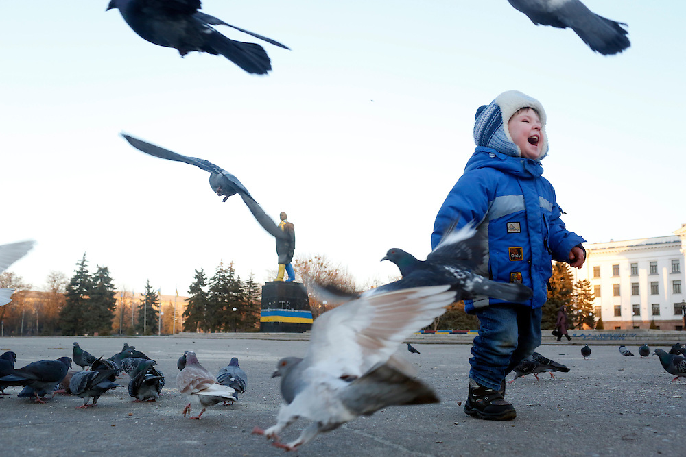 Children play with pigeons in Lenin Square on February 11, 2015 in Kramatorsk, Donetsk Oblast, Ukraine. Kramatorsk was the site of deadly shelling the previous day that killed and injured civilians and soldiers.
