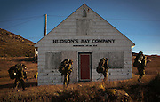 Canadian soldiers pass by an old Hudson's Bay trading post while taking part in maneuvers on Baffin Island in the Canadian Arctic. Apex, Nunavut. (2009)