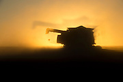 Last light and dust creates a double image of a header harvesting wheat in the Western Australian Wheatbelt. Wyalkatchem, Western Australia  08 December 2012 - Photograph by David Dare Parker