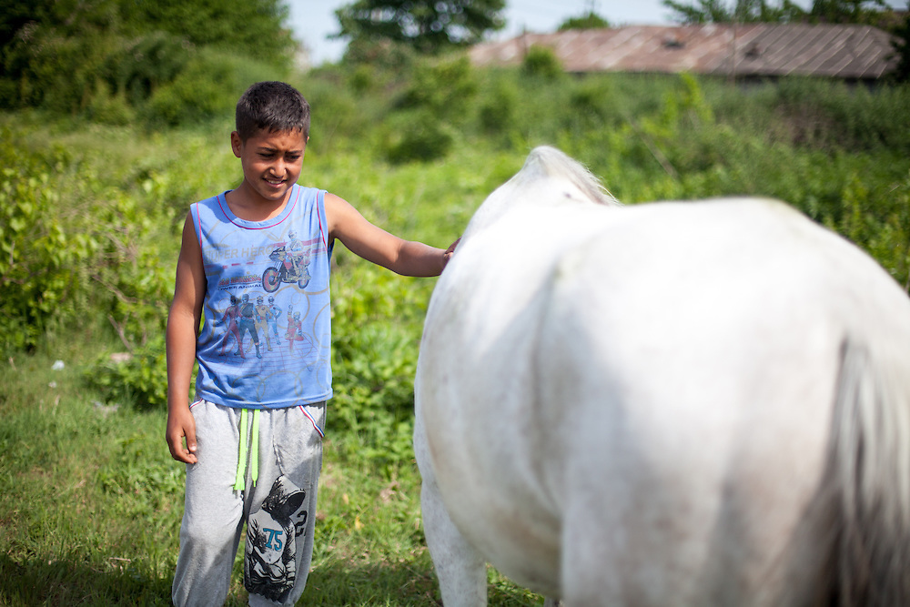 "Young Roma man with a white horse named ""Gina"" in the Roma area of Frumusani."