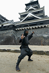 Ninja warrior posing in front of famous Kumamoto Castle in Kyushu Japan