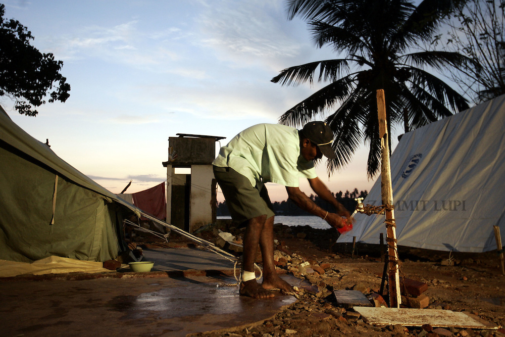 A man with a bandaged foot takes some water in the tsunami-devastated area of Galle, south west coast of Sri Lanka, January 13, 2005..Photo by Darrin Zammit Lupi