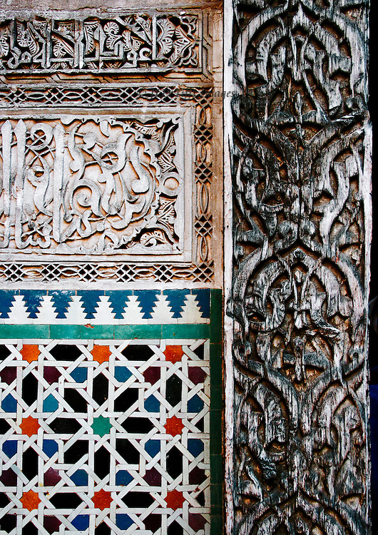 Fes: el Attarine Medersa; tile and carved wood decoration on interior walls, in geometric panels each filled with a different group of motifs.