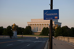"""A sign welcoming visitors on the Arlington Memorial Bridge to Washington, DC with the Lincoln Memorial in the background.  The Lincoln Memorial is located on the National Mall in Washington, D.C. It is a United States Presidential memorial built to honor the 16th president of the United States, Abraham Lincoln. The architect was Henry Bacon, the sculptor was Daniel Chester French, and the painter of the interior murals was Jules Guerin...The building is in the form of a Greek Doric temple and contains a large seated sculpture of Abraham Lincoln and inscriptions of two well-known speeches by Lincoln. The memorial has been the site of many famous speeches, including Martin Luther King's """"I Have a Dream"""" speech, delivered on August 28, 1963, during the rally at the end of the March on Washington for Jobs and Freedom...Like other monuments on the National Mall, including the nearby Vietnam Veterans Memorial, Korean War Veterans Memorial, and National World War II Memorial, the Lincoln Memorial is administered by the National Park Service under its National Mall and Memorial Parks group. The National Memorial has been listed on the National Register of Historic Places since October 15, 1966. It is open to the public 24 hours a day. In 2007, it was ranked seventh on the List of America's Favorite Architecture by the American Institute of Architects."""