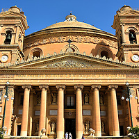 Full Frontal View of Mosta Dome in Mosta, Malta <br /> The Church of the Assumption of Our Lady dominates the center of Mosta, a small town of about 20,000 people in the center of Malta. When St Marija Assunta was consecrated in 1871 the town&rsquo;s population was 90% smaller.  So it is a delightful surprise to see gorgeous neoclassical architecture here.  Among its features are ten Ionic columns that form the portico, the pediment with its delicate reliefs and two flanking bell towers. Even more surprising?  It has the world&rsquo;s fourth largest unsupported dome! That is why the Roman Catholic church is proudly called The Mosta Dome.