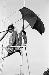 BANGLADESH TANGAIL APR94 - A fisherman sits atop his bamboo net lifting apparatus, sheltered from the harsh sunlight by a black umbrella in rural Tangail, Bangladesh...jre/Photo by Jiri Rezac..© Jiri Rezac 1994