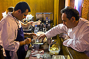 Ferran Adrià, (at right)  a chef at the famous El Bulli restaurant near Rosas on the Costa Brava in Northern Spain helps another chef prepare a meal. (Ferran Adrià is featured in the book What I Eat: Around the World in 80 Diets.)