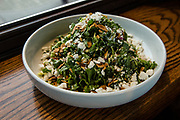Astoria, NY - 8 December 2016. A kale and brussels sprouts salad, with toasted almonds, ricotta salata (ricotta cheese that has been pressed, salted, and dried), apple and red onion at The Pomeroy.