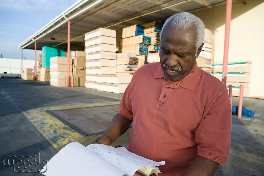 Senior man with clipboard outside warehouse full of wood
