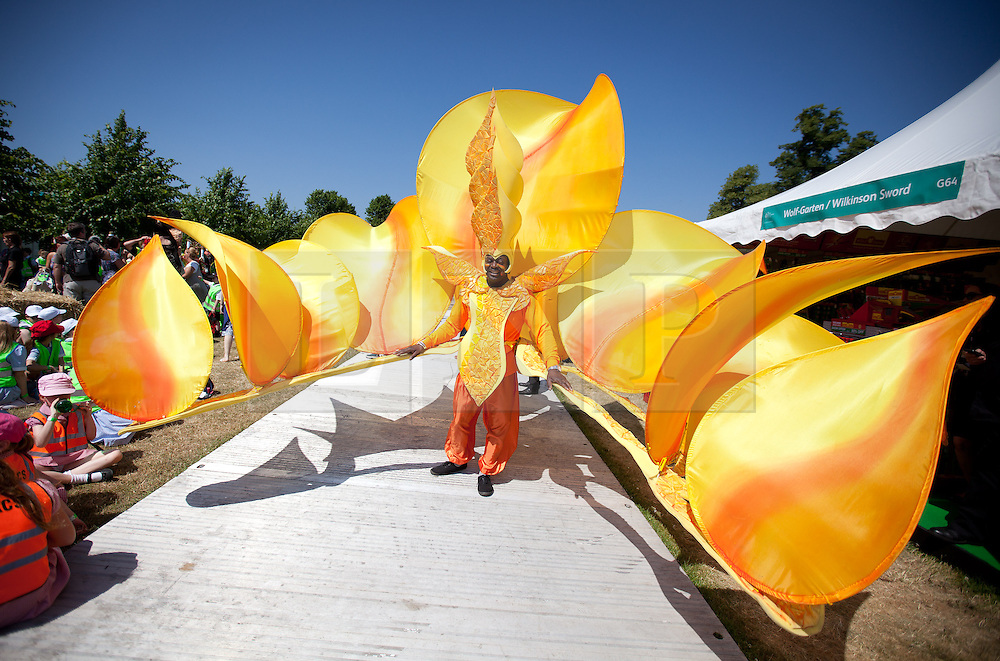 © Licensed to London News Pictures. 08/07/2013. London, UK. A brightly coloured carnival dancer is seen at the press view for the Royal Horticultural Society's Hampton Court Palace Flower Show today (08/07/2013). Photo credit: Matt Cetti-Roberts/LNP