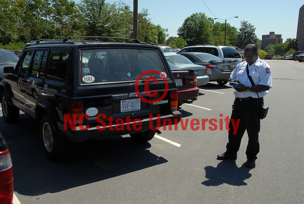 Parking control officer writes up a parking ticket. PHOTO BY ROGER WINSTEAD