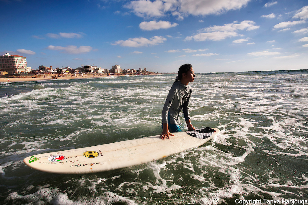 14 year old  Sabah Abu Ghanim, Gaza's famous girl surfer, waits to catch a wave.