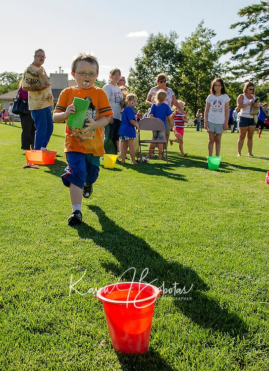 Jayden Grady-Hayward fills his bucket for the sponge race during Opechee Day Camp's Peanut Festival Thursday evening.  (Karen Bobotas/for the Laconia Daily Sun)