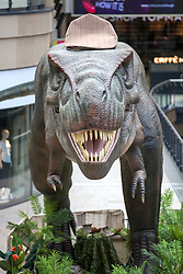 "© Licensed to London News Pictures. 01/08/2018. Leeds UK. The UK's largest animatronic T-Rex is wearing a flat cap this morning to celebrate Yorkshire Day. The 3-Tonne 8 metre tall predator is currently on display at the Trinity shopping centre in Leeds & is today wearing a giant flat cap & being renamed ""Tyke-Rex"" for the day in honour of the Yorkshire dialect. Photo credit: Andrew McCaren/LNP"