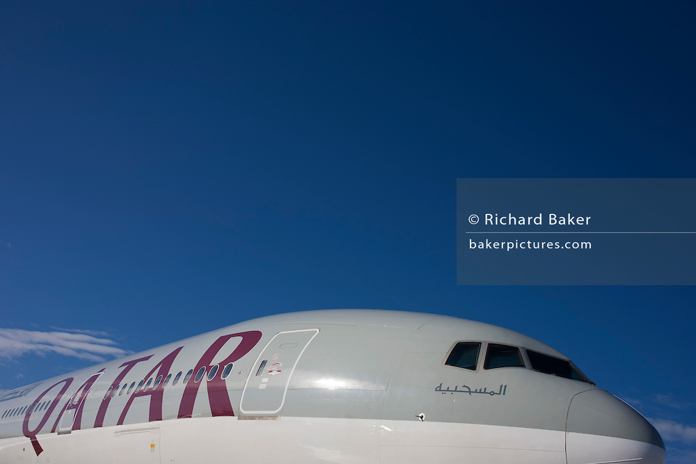 A boeing 777ER (Extended Range) airliner belonging to the airline Qatar Airways, that is based in the Gulf State. Placed low in the picture to emphasize the blue airspace above, we see it's two-tone coloured nose and cockpit with arabic writing below one pilot's windscreen. Along the fuslage is the company logo written in English.