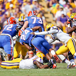 Oct 12, 2013; Baton Rouge, LA, USA; Florida Gators running back Matt Jones (24) is tackled by LSU Tigers safety Craig Loston (6) and defensive tackle Ego Ferguson (9) during the first quarter of a game at Tiger Stadium. Mandatory Credit: Derick E. Hingle-USA TODAY Sports