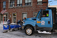 Merrick, New York, USA. January 24, 2016. After Nor'easter drops more than two feet of snow on south shore of Nassau County, Long Island, Town of Hempstead Highway Department employees operate snow plows, including truck with blade attached, to remove about 25 inches of snow blanketing downtown streets and public parking, including for the Merrick United States Post Office.