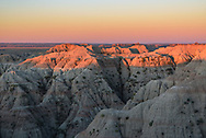 The first light of sunrise paints the top of the badlands with a brilliant orange glow. Located in western South Dakota on the edge of the Great Plains, this harsh landscape is home to bison, bighorn sheep, pronghorn antelope, prairie dogs, and other wildlife. By definition badlands are semiarid regions with sparse vegetation that experience high rates of erosion. Even though there are other places in the western US and throughout the world known as badlands, the term originated here in Badlands National Park. This is a special place, but unfortunately the person who decided to use it as a landfill didn't think so. When I peered into this steep ravine I spotted a couch that someone had rolled to the bottom.