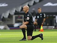 Referee Anthony Taylor takes the knee during the Premier League match at the London Stadium, London. Picture date: 20th June 2020. Picture credit should read: David Klein/Sportimage