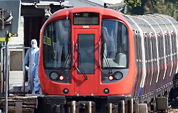 EDITORS NOTE: IMAGE SHOT THROUGH CONSIDERABLE HEAT HAZE © Licensed to London News Pictures. 15/09/2017. London, UK. A forensics officer can be seen next to the evacuated tube train at Parsons Green Station after a small explosion during the morning rush hour. A number of casualties have been reported. Photo credit: Peter Macdiarmid/LNP