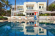 Tommy Hilfiger Lists Colorful, Eye-Candy Estate for $27.5M<br /> <br /> 605 Ocean Blvd. in Golden Beach, FL, 33160, the home of internationally renowned fashion mogul Tommy Hilfiger and his wife Dee Hilfiger, for $27.5 million. <br /> <br /> The 14,079-square-foot beachfront estate is completely designed by acclaimed interior designer Martyn Lawrence Bullard to the Hilfigers' tastes, and features a design of art gallery/1960s/1970s style.<br /> <br /> Agents The Jills sold the estate to the Hilfigers in 2013.<br /> Boasting breathtaking direct ocean views and 100 feet of water frontage, the estate features seven bedrooms, eight bathrooms, four half bathrooms, and an elevator. Situated on a lush  27,500-square-foot lot, the estate offers a large oceanfront infinity pool as well as beautiful palms presiding over the private beach. It is one of a very small number of beachfront homes in exclusive Golden Beach, a luxury community home to many celebrities.  Additional property details include:<br /> Designed with a polychrome motif, the estate, featured in the September 2014 issue of Architectural Digest, is a palace of whimsical color, eclectic furnishings and vibrant Pop and post-Pop art.  <br /> The bright and airy estate welcomes with clean white walls and white-glass tiles, accentuated by a black marble central staircase. <br /> In the center of the home is the spacious living room, highlighted by a hair-on-hide carpet featuring vivid swirls. Black and white stripes don the kitchen floor.<br /> The bedrooms entice with bright and bold colors and patterns. Scratch-and-sniff fruit wallpaper covers the walls of several of the guest bathrooms.  <br /> Tommy's private office pays homage to the Hilfiger brand, with a montage of blue and red wall panels with white reveals. <br /> 