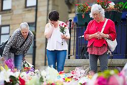 © Licensed to London News Pictures. 22/06/2016. Birstall UK. A lady leaves a card & flowers in Birstall market square on what would have been MP Jo Cox's 42nd birthday today. The MP Jo Cox was murdered last week in Birstall. Photo credit: Andrew McCaren/LNP