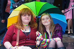 London, June 28th 2014. Two girls shelter from the rain as Gay Pride revellers assemble on Baker Street ahead of the parade.