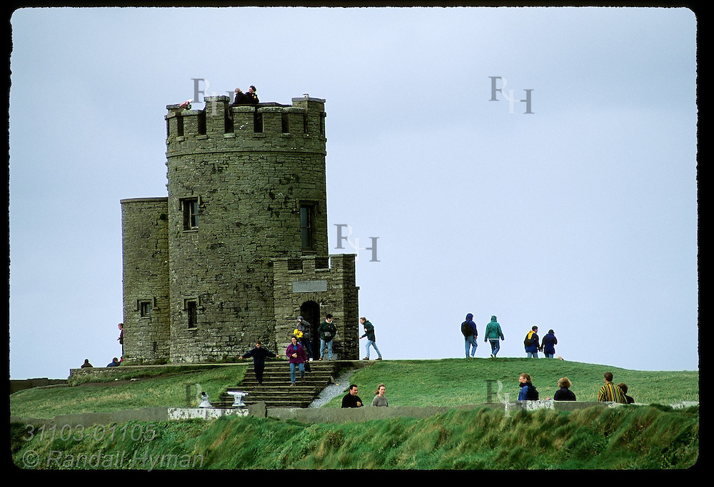 Visitors walk near O'Brien's Tower, built for Victorian tourists as a prime viewing spot atop the Cliffs of Moher; Ireland.