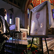 pope mass - des moines, april 7 -- Lazaro Contreras, from Des Moines, stands before a portrait of Pope John Paul II Thursday at St. Ambrose Church in downtown Des Moines.  Contreras, who had arrived early before the evening Mass, had just signed the book next to the Pope's portrait.  photo by david peterson  mi