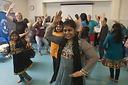 Dancer Vindhya Katta demonstrates Nachale: The Bollywood Dance Workout with all the attendees during the English Conversation Club: Dance and Dialogue event Saturday April 9, 2011 at the Iroquois Branch of the Louisville Free Public Library in Louisville, Ky. Henna and Bindi followed the Bollywood dance lesson, and then volunteers were paired with English language learners to work on conversation skills. (Photo by Brian Bohannon)