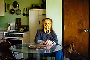 Kenneth Morrison wearing a mask in his kitchen with his dog looking at him